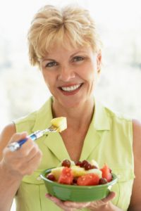 Middle Aged Woman Eating Fresh Fruit Salad